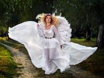 Jeune femme utilisant de longues ailes blanches de robe et d'ange image stock