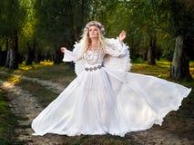 Jeune femme utilisant de longues ailes blanches de robe et d'ange photos libres de droits