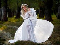 Jeune femme utilisant de longues ailes blanches de robe et d'ange images libres de droits