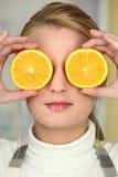 Jeune femme utilisant des moitiés oranges comme yeux Images stock