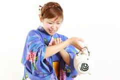 Jeune femme utilisant le kimono japonais avec la bobine de moustique, mordue par le moustique Photo stock