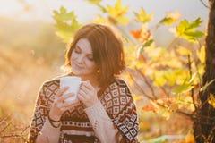 Jeune femme utilisant le poncho tricoté ayant le pique-nique dans une forêt : thé potable et sélection des pommes Photographie stock