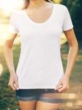 Jeune femme utilisant le T-shirt et les blues-jean vides dedans photo stock