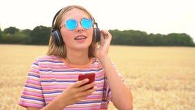 Jeune femme utilisant les lunettes de soleil bleues dans un domaine écoutant la musique sur les écouteurs sans fil clips vidéos