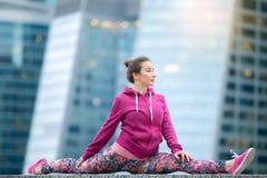 Jeune femme utilisant les vêtements de sport roses dans la pose de Dieu de singe Photo libre de droits