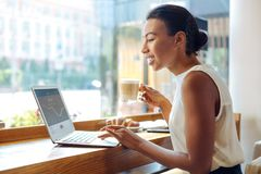 Jeune femme vérifiant l'application et buvant du latte en café Photographie stock libre de droits