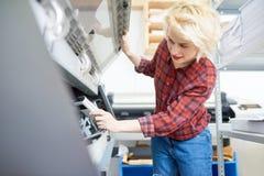Jeune femme vérifiant l'imprimante images libres de droits