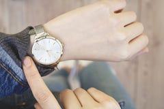 Jeune femme vérifiant le temps sa montre images stock