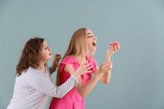 Jeune femme vaillante essayant d'arrêter son ami mince de manger le beignet sur le fond de couleur Concept de nourriture de r?gim photos stock