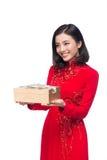 Jeune femme vietnamienne dans la robe d'ao Dai tenant le boîte-cadeau image stock
