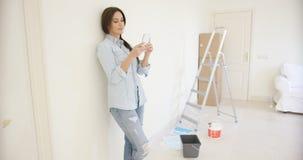 Jeune femme vérifiant un message textuel Photographie stock