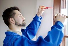 Jeune fenêtre de réparation de bricoleur avec le tournevis Photographie stock libre de droits