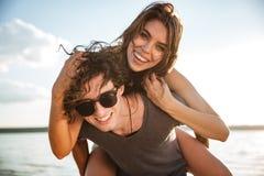 Jeune ferroutage heureux de couples à la plage Images libres de droits