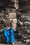 Jeune fille à côté d'une roche en pierre dans une robe bleue Image libre de droits
