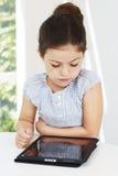 Jeune fille à l'aide du comprimé Photo libre de droits