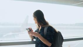 Jeune fille à l'aide du smartphone près de la fenêtre d'aéroport La femme européenne heureuse avec le sac à dos emploie l'APP mob Images libres de droits