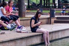 Jeune fille à l'ombre détendant avec des jambes dans l'eau Images stock