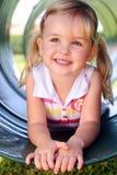 Jeune fille à la cour de jeu Photographie stock libre de droits