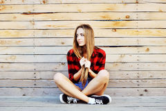 Jeune fille à la mode posant sur le fond en bois de mur moderne Photos stock