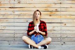 Jeune fille à la mode posant sur le fond en bois de mur moderne Photographie stock libre de droits