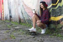 Jeune fille à la mode s'asseyant avec du café et une planche à roulettes Photo libre de droits