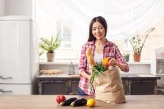 Jeune fille à la position saine de mode de vie de cuisine prenant l'orange du sac avec des produits heureux photos stock