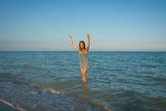 Jeune fille éclaboussant l'eau en mer Images stock
