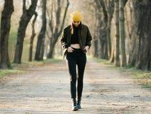 Jeune fille élégante avec le dessus de ventre marchant sur une avenue photos stock