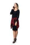 Jeune fille élégante décontractée dans la robe noire riant au téléphone recherchant Images libres de droits