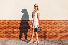 Jeune fille élégante dans des lunettes de soleil dans une jupe rose avec un noir images stock