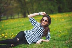 Jeune fille élégante dans une chemise de plaid et des lunettes de soleil se trouvant sur l'herbe verte au printemps Image libre de droits