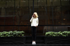 Jeune fille élégante et mince se tenant près du restaurant et parlant au téléphone Photographie stock