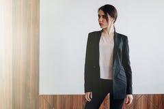 Jeune fille émotive attirante dans des vêtements de style des affaires sur un fond blanc simple dans un bureau ou une assistance photographie stock