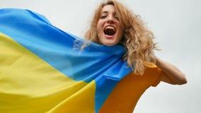 Jeune fille émotive heureuse avec le drapeau ukrainien bleu et jaune au-dessus du fond de ciel banque de vidéos