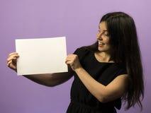 Jeune fille étonnée de brune tenant le conseil blanc vide vide Présentation de tract Mains de prise de brochure Exposition de fil photos stock