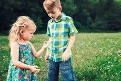 Jeune fille adorable tenant la sauterelle Photo stock