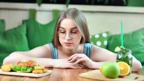 Jeune fille affamée sur le régime faisant le choix entre les aliments de préparation rapide et le plan rapproché moyen de fruits  banque de vidéos
