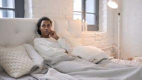 Jeune fille africaine de pensée songeuse s'étendant dans le lit clips vidéos