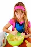 Jeune fille aidant en gâteau de traitement au four Images stock
