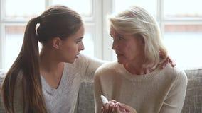 Jeune fille aimante consolant la vieille mère pleurante triste pour donner l'appui banque de vidéos