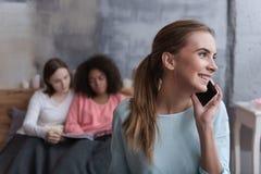 Jeune fille amusée parlant au téléphone à la maison Photos stock