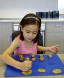 Jeune fille aplatissant des boules de pâte de biscuit. Photos stock