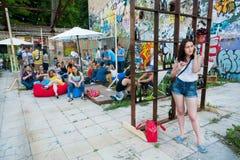 Jeune fille appelle le téléphone dans la foule de la barre d'outddor Photo libre de droits