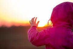 Jeune fille appelle sa main au coucher du soleil Image stock