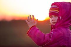 Jeune fille appelle sa main au coucher du soleil Images stock