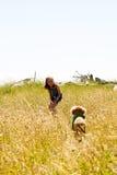 Jeune fille appelle son chiot dans un domaine d'herbe Images stock