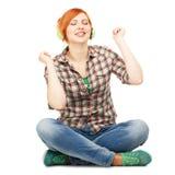 Jeune fille appréciant écouter la musique sur des écouteurs Images stock