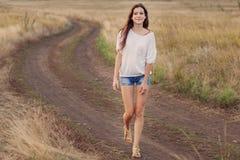 Jeune fille appréciant dehors la nature Elle marchant le long de la route photos libres de droits