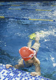 Jeune fille apprenant à nager dans la piscine avec des nageoires Image libre de droits