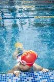 Jeune fille apprenant à nager dans la piscine avec des nageoires Photographie stock libre de droits